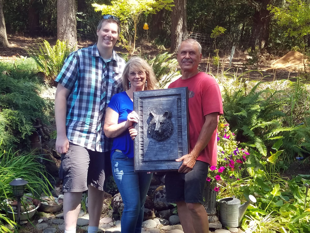 Mark Boehly - Vicki & Gary Garland with Karbon Kast bear - Art by Graphicsbyte Creative and Truax Designs